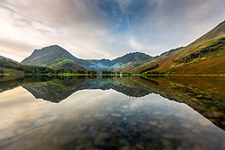 © Licensed to London News Pictures. 15/09/2020. Buttermere UK. The surrounding mountains reflect into the still water of Buttermere lake in Cumbria this morning. Photo credit: Andrew McCaren/LNP