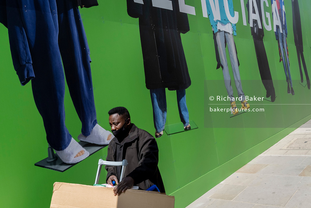 A delivery man pushes his load beneath the temporary construction hoarding for Balenciaga, a retail space which is opening soon on Bond Street, on 27th April 2021, in London, England. Balenciaga is a fashion house founded in 1917 by Spanish designer Cristóbal Balenciaga in San Sebastián, Spain.