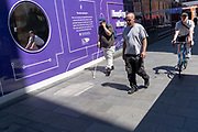 Pedestrians walk and a cyclist pedals past a purple hoarding that screens off refurburshment works in the West End's Leicester Square, on 16th July 2021, in London, England.