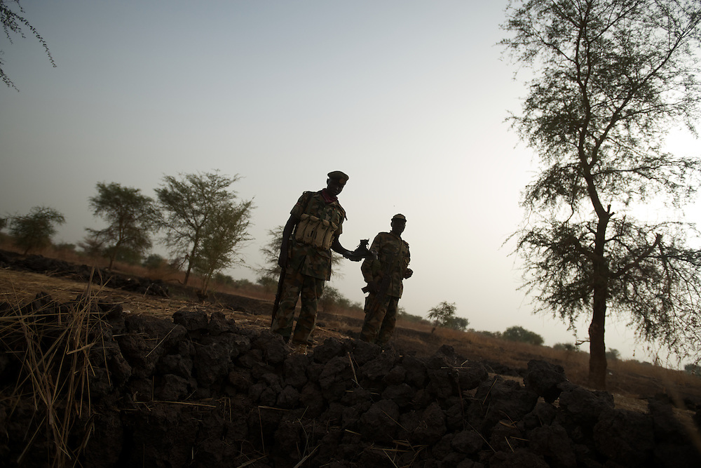 April 24, 2012 - Panakuach, South Sudan: A group of SPLA soldiers stand at the scene where a bomb dropped by the SAF air force landed minutes earlier near the last defensive line outside the village of Panakuach, 70 kilometers north of Bentiu...South Sudan and their northern neighbors, Sudan, have in the past two weeks been involved in heavily clashes over border disputes. Bentiu and neighboring villages have been under constant bombardment by the troops os Karthoum , who established their positions around 10 kilometers into South Sudan's territory. The international community is concerned about the possibility of a full on war between the two countries. (Paulo Nunes dos Santos/Polaris)