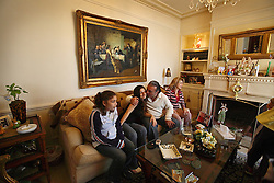 The Hakim family, Tamura, 15, Tatiana, 16, dad Jamie and mom Elaine relax in their home after school, Beirut, Lebanon, March 30, 2006. The father is Sunni Muslim and mother is Maronite Christian. Although Elaine technically converted to Sunni for the wedding, the family still celebrates Christian holidays, in addition to the Muslim ones.