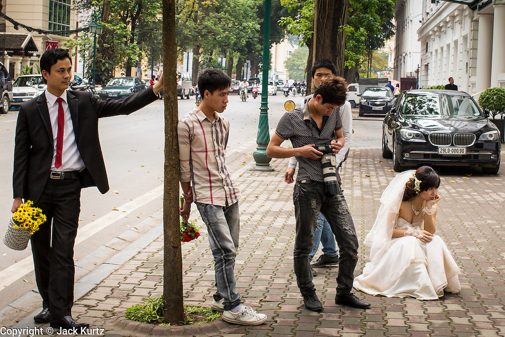 09 APRIL 2012 - HANOI, VIETNAM:  A couple and their photographer wait on a street for a space to be photographed in Hanoi, the capital of Vietnam. Hanoi, established in 1010 AD, is one of the oldest permanent cities in Southeast Asia. Most of the wedding photographers in Hanoi work on a street in front of the Metropole Hotel using the luxury brand store fronts, like Cartier and Panerai as backgrounds to their photos.       PHOTO BY JACK KURTZ