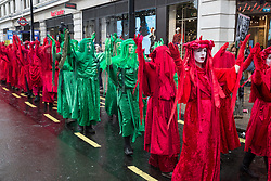 London, UK. 12 October, 2019. The Red and Green Brigades lead thousands of fellow climate activists from Extinction Rebellion on the XR funeral march from Marble Arch to Russell Square on the sixth day of International Rebellion protests to demand a government declaration of a climate and ecological emergency, a commitment to halting biodiversity loss and net zero carbon emissions by 2025 and for the government to create and be led by the decisions of a Citizens' Assembly on climate and ecological justice. Credit: Mark Kerrison/Alamy Live News