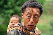 Bhutanese man with baby in a village not far from Thimphu. The man's lips are stained red from chewing betel nut. Bhutan.