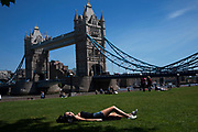 Woman sleeping near to Tower Bridge ay Potters Fields Park. This newly created green space is now popular with tourists and others to come for a summer rest with this great iconic London landmark as the backdrop.