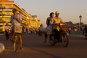 A Cambodian man stops to light a cigarette while biking around the riverfront of Phnom Penh, Cambodia.