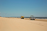 NC01408-00...NORTH CAROLINA - Trucks cruising along the beach north of Corrola like it is a major highway. Trucks are on the beach for recreation, fishing, to service the houses and to view the wild horses.