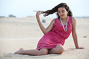 Young 12 year old teen in red dress on the beach. Model released
