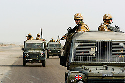"British soldiers from The East and West Riding Regiment, Territorial Army wearing desert camouflage, Kevlar helmet and body armor, carrying SA80 assault rifle which is fitted with SUSAT sights, Travel in convoy in  ""Soft Skin"" Land Rovers with troops manning the top cover position. The convoy is moving from Basra Air Station to Shibah Logistics Base  during Op-Telic in March 2005"