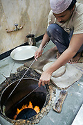 L M Rahman preparing and cooking fresh naan bread in the tandoor oven at Karim's Restaurant, Delhi, India