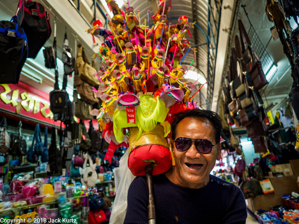 10 JULY 2018 - NAKHON PATHOM, THAILAND: A toy seller walks through the market in Nakhon Pathom. Nakhon Pathom is about 35 miles west of Bangkok. It is one of the oldest cities in Thailand, archeological evidence suggests there was a settlement on the site of present Nakhon Pathom in the 6th century CE, centuries before the Siamese empires existed. The city is widely considered the first Buddhist community in Thailand and the nearly 400 foot tall Phra Pathom Chedi is considered the first Buddhist temple in Thailand.     PHOTO BY JACK KURTZ