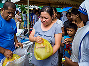 29 JANUARY 2018 - CAMALIG, ALBAY, PHILIPPINES: An evacuee from Barangay Gapo picks up donated rice and clothing in a small shelter for people evacuated from Mayon volcano in Camalig. The Missionaries of Charity visited the shelter to hand out food and clothes. A woman at the shelter said they were out of clean drinking water and several people had come down with diarrhea and other stomach ailments. There are only 206 people at the shelter, many of the shelters have over 1,000 residents. Mayon volcano's eruptions continued Monday. At last count, more 80,000 people have been evacuated from their homes of the slopes of the volcano and are crowded into shelters in communities outside of the danger zone.    PHOTO BY JACK KURTZ