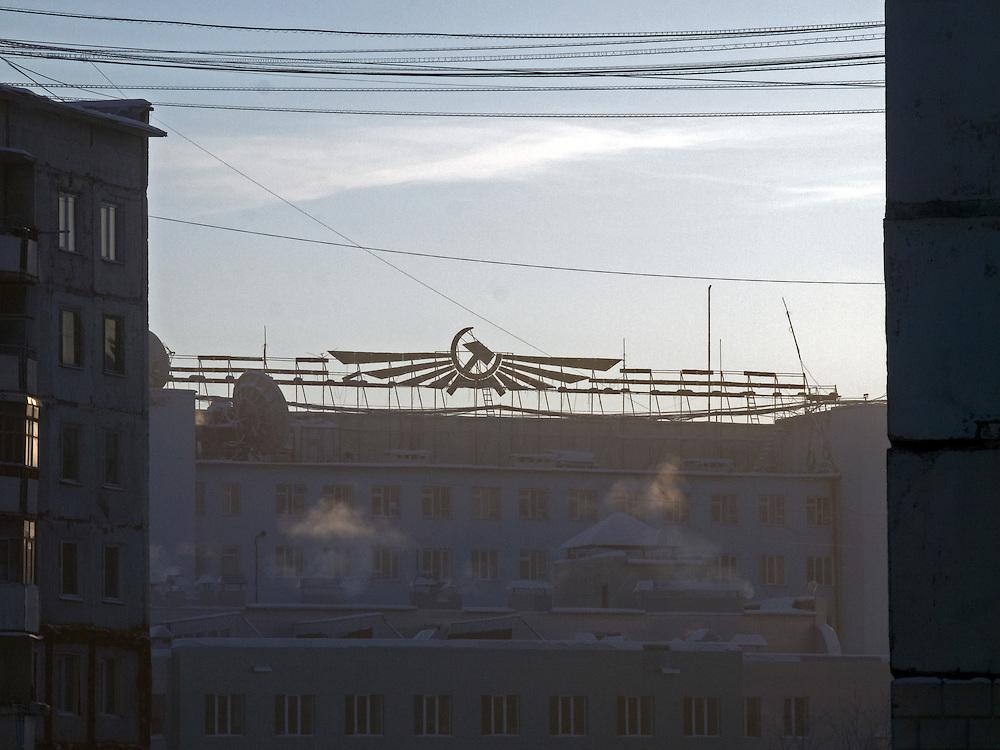 Hammer und Sichel als Symbole vergangener Zeiten zwischen Plattenbauten im Zentrum von Jakutsk. Jakutsk hat 236.000 Einwohner (2005) und ist Hauptstadt der Teilrepublik Sacha (auch Jakutien genannt) im Foederationskreis Russisch-Fernost und liegt am Fluss Lena. Jakutsk ist im Winter eine der kaeltesten Grossstaedte weltweit mit bis zu durchschnittlichen Wintertemperaturen von -40.9 Grad Celsius.<br /> <br /> Symbols of the former Soviet Union on a building in between panel houses in Yakutsk. Yakutsk is a city in the Russian Far East, located about 4 degrees (450 km) below the Arctic Circle. It is the capital of the Sakha (Yakutia) Republic (formerly the Yakut Autonomous Soviet Socialist Republic), Russia and a major port on the Lena River. Yakutsk is one of the coldest cities on earth, with winter temperatures averaging -40.9 degrees Celsius.
