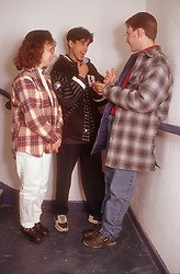 Group of teenagers with hearing impairments standing in corridor using sign language to communicate,