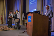 Purchase, NY – 31 October 2014. Yonkers High School presenting on stage. (Left to rioght: Anthony Doqaj,  Erik Kantar, Fareed Ibrahim, Geri Shentoli.) At the podiium is Melvin Burruss, Chairman of the Afrian American Men of Westchester. The Business Skills Olympics was founded by the African American Men of Westchester, is sponsored and facilitated by Morgan Stanley, and is open to high school teams in Westchester County.