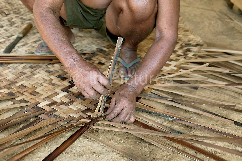 A Khmu man weaving a bamboo mat outside his home in Ban Yangneua, Phongsaly province, Lao PDR. Renowned for their superior basket weaving skills, the Khmu belong to the Mon-Khmer language group considered to be the original inhabitants of Laos and are the largest ethnic minority with many sub-groups resident in all provinces of Northern Laos. Ban Yangneua has been temporarily relocated away from the Nam Ou river due to the construction of the Nam Ou Cascade Hydropower Project Dam 5.