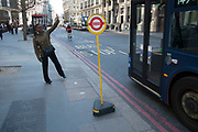 Street scene of a woman flagging a bus at a temporary bus stop in the City of London, England, United Kingdom.