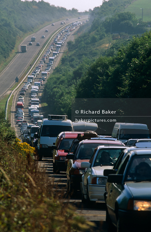 The A30 highway runs deep into the South-West of England - from Exeter in the county of Devon to Penzance in the narrow peninsular of Cornwall. On certain dates in the calendar routes like this, near the Cornish town of Bodmin, England, come to a standstill from the huge volume of cars and private vehicles, all heading down to costal resorts and better weather. We see here a huge tailback of traffic that is queueing along one side of the British dual-carriageway (two lanes in each direction) from close-up  to the distance down and up a natural hill in this undulating landscape. The cars have edged forward are nose to tail for hours in summer heatwave and tempers fray, children arguing in the back and an otherwise relaxed holiday mood suddenly goes bad.