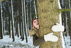 Teenage girl hugging a tree in a forest, Bavaria, Germany