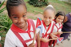Young girls wearing school uniform and waving national flags in Havana; Cuba,