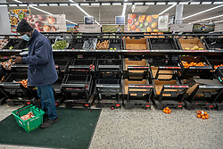 © Licensed to London News Pictures. 21/12/2020. London, UK. Shoppers look at empty shelves in the fruit and veg aisles at Asda in London this afternoon. Chaotic scenes at Asda in Wandsworth, South West London as a huge rush of shoppers descended on the store causing long queues in the aisles after news that French customs blocked freight from leaving Dover to France after a Covid-19 mutation caused a rapid increase of infection throughout the capital and South East of England. Last week Prime Minister Boris Johnson put London and parts of the South East into Tier 4 lockdown after the new Covid-19 mutation was discovered. Photo credit: Alex Lentati/LNP