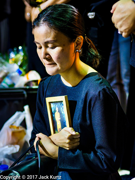 13 OCTOBER - BANGKOK, THAILAND:   A woman holds a portrait of the late King and prays on the first anniversary of the death of Bhumibol Adulyadej, the Late King of Thailand. About 199 monks from 14 Buddhist temples in Bangkok participated in the mass merit making at Siriraj Hospital to mark the anniversary of the revered King's death. He will be cremated on 26 October 2017.  PHOTO BY JACK KURTZ
