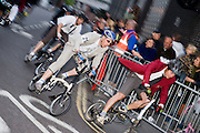 Cyclists, some in suits and on folding bikes and others professionals, racing in the evening at the annual Smithfield Nocturne, London.