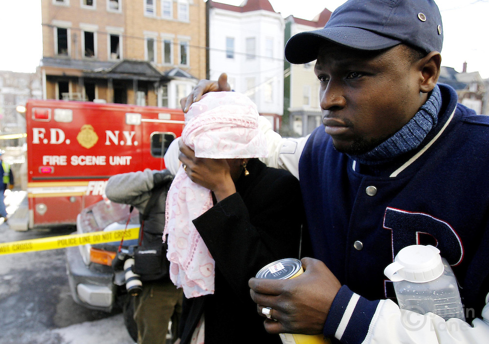 Two people walk past a house (L) where 9 people were killed, 8 of them children, in an overnight fire in the Bronx, New York on Thursday 08 March 2007. The two entered a nearby house where members of the family were gathering.
