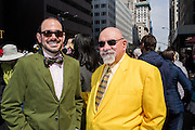 New York, NY, USA-27 March 2016. Two hatless but well-dresed men, one wearing a bright yellow suit, in the  annual Easter Bonnet Parade and Festival.