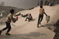 Licensed to London News Pictures. 08/11/2016. Qayyarah, Iraq. Iraqi children use rubbish to sled down a destroyed ISIS headquarters, located in a football stadium, that was hit by a coalition airstrike, in the town of Qayyarah, Iraq. Oil wells in and around the town of Qayyarah, Iraq, we set alight in July 2016 by Islamic State extremists as the Iraqi military began an offensive to liberated the town.<br /> <br /> For two months the residents of the town have lived under an almost constant smoke cloud, the only respite coming when the wind changes. Those in the town, despite having been freed from ISIS occupation, now live with little power, a water supply tainted with oil that only comes on periodically and an oppressive cloud of smoke that coats everything with thick soot. Many complain of respiratory problems, but the long term health implications for the men, women and children living in the town have yet to be seen. Photo credit: Matt Cetti-Roberts/LNP