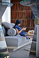 A vietnamese woman lies comfortably on a sofa of Sheraton hotel in Nha Trang, Vietnam, Asia. She texts on her cell phone and drinks a beer.