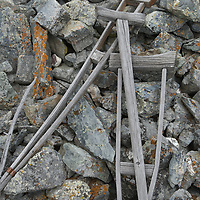 """An offering of abandoned crutches (possibly from a deceased person) lies atop an """"ovo"""" monument near ancient petroglyphs above northern Mongolia's Lake Dood Noor.  Spiritual offerings like these arise from a blend of Tibetan Buddhism, Animism and Shamanism"""