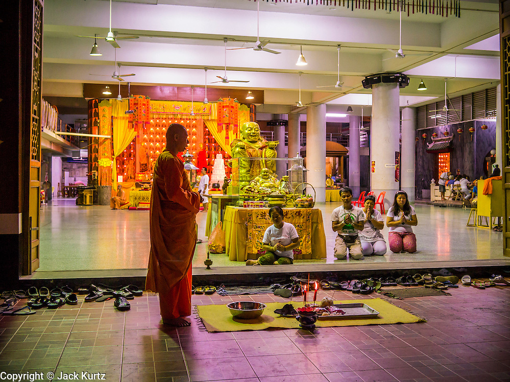 02 NOVEMBER 2012 - HAT YAI, SONGKHLA, THAILAND: A Buddhist monk leads a prayer at the entrance to Wat Ta Won Vararum in Hat Yai, Songkhla, Thailand. Hat Yai is the commercial center of south Thailand and a popular weekend vacation destination for Malaysian and Singaporean tourists.    PHOTO BY JACK KURTZ