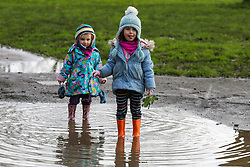 © Licensed to London News Pictures. 05/02/2021. London, UK. Gwendolyn Rixon age 4 (L) and Josephine Rixon age 2 (R) walk through a large puddle of water in Chestnuts Park, north London. Part of the footpath in the park is flooded following heavy overnight rain in London. According to the Met Office, snow is forecast for the weekend. <br /> <br /> ***Permission Granted***<br /> <br />  Photo credit: Dinendra Haria/LNP