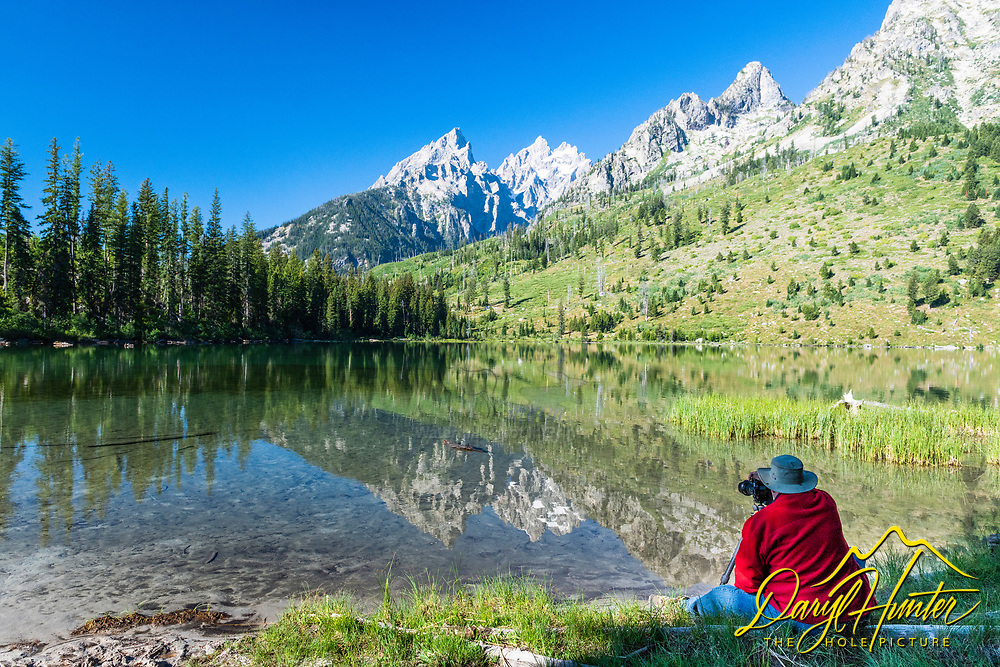 Landscape photographer in red, reflection, String Lake, Grand Teton National Park.