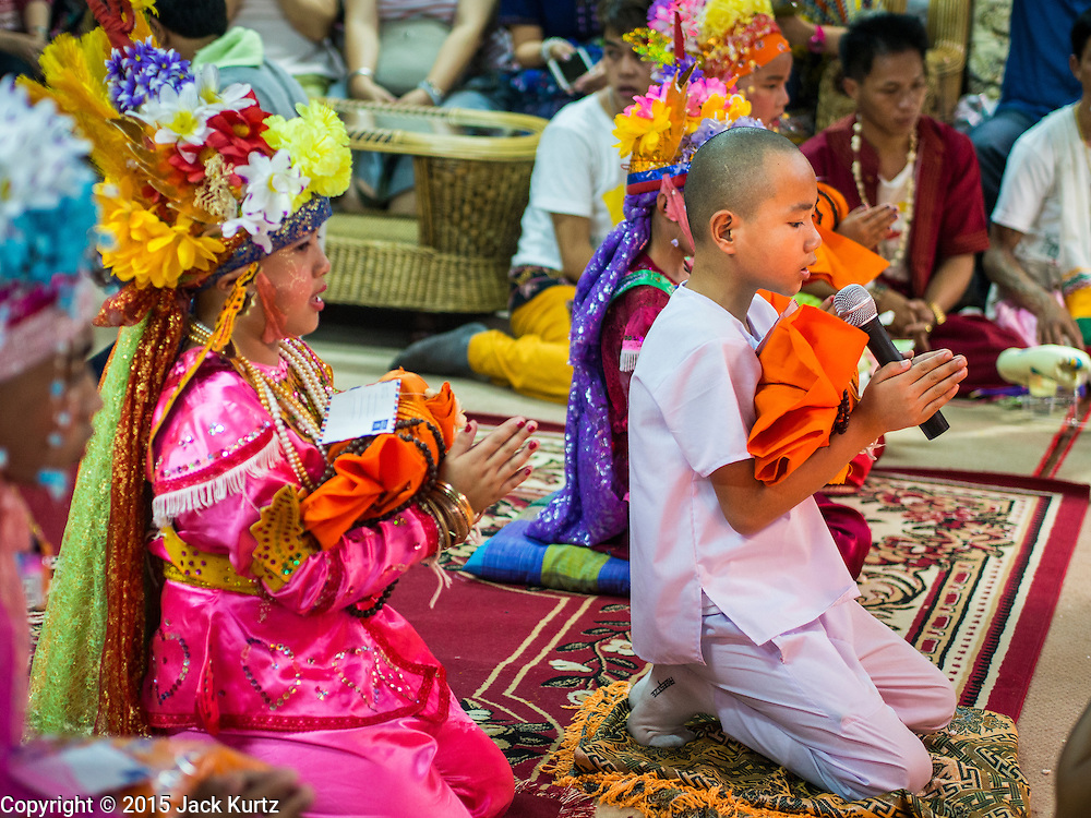 """06 APRIL 2015 - CHIANG MAI, CHIANG MAI, THAILAND: Boys pray with their monk's robes during their ordination on the last day of the three day long Poi Song Long Festival in Chiang Mai. The Poi Sang Long Festival (also called Poy Sang Long) is an ordination ceremony for Tai (also and commonly called Shan, though they prefer Tai) boys in the Shan State of Myanmar (Burma) and in Shan communities in western Thailand. Most Tai boys go into the monastery as novice monks at some point between the ages of seven and fourteen. This year seven boys were ordained at the Poi Sang Long ceremony at Wat Pa Pao in Chiang Mai. Poy Song Long is Tai (Shan) for """"Festival of the Jewel (or Crystal) Sons.   PHOTO BY JACK KURTZ"""