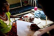 Health care staff check on a child diagnosed with Malaria.