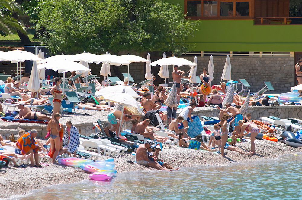 Crowds of tourists on the beach by the sea. Deck chairs, sun shade umbrellas... Uvala Sumartin bay between Babin Kuk and Lapad peninsulas. Dubrovnik, new city. Dalmatian Coast, Croatia, Europe.
