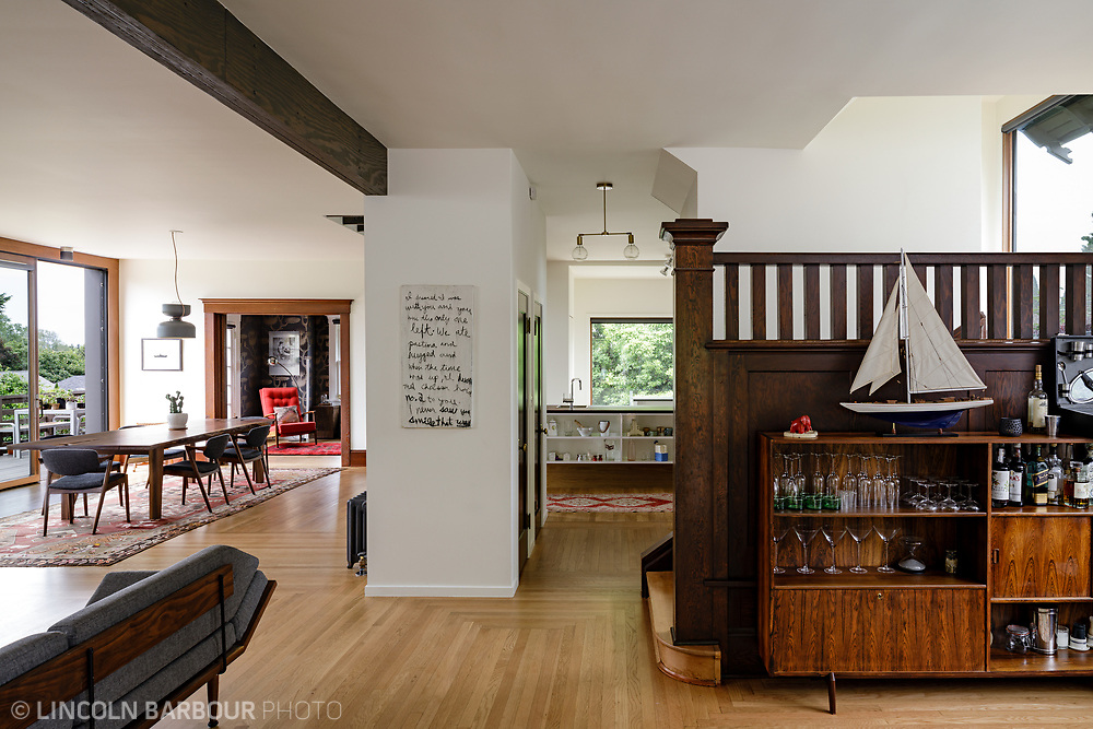 A remodeled craftsmen home interior showing a bar, dining room and the kitchen in the background.