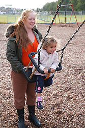 Woman pushing girl on a swing