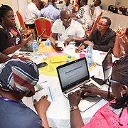 INDIVIDUAL(S) PHOTOGRAPHED: From left to right: N/A, Falicia Akan, Ibiam Azu Agwu, Lovelyn Eteng, Dr. Offor Jonah Bassay, unknown, Iyala Okara Godwin, and Odey Lucy. LOCATION: Financing Workshop, Lagos, Nigeria. CAPTION: Workshop participants sat around round tables to facilitate discussions on how to improve approaches to financing Nigeria's health care sector.