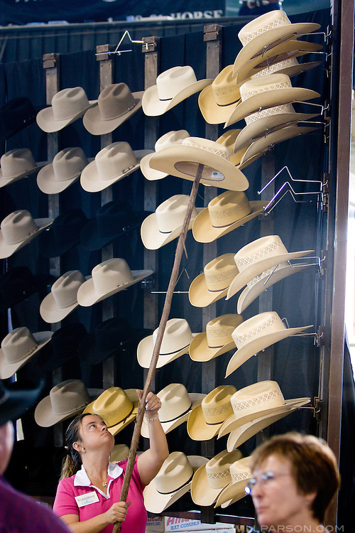 A vendor sells cowboy hats while Chris Cox, professional horse trainer, demonstrates his techniques for a crowd in Los Angeles on September 15, 2007.