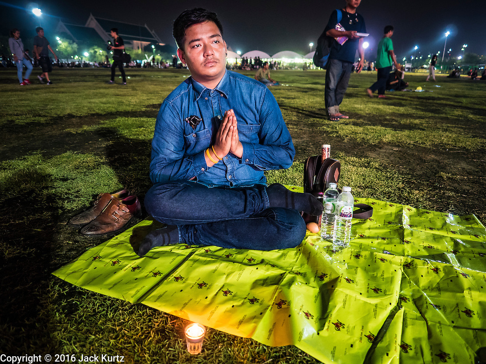 17 OCTOBER 2016 - BANGKOK, THAILAND:  Mourners honoring Bhumibol Adulyadej, the King of Thailand, pray on Sanam Luang, near the Grand Palace. Thai King Bhumibol Adulyadej died Oct. 13, 2016. He was 88. His death comes after a period of failing health. Bhumibol Adulyadej, was born in Cambridge, MA, on 5 December 1927. He was the ninth monarch of Thailand from the Chakri Dynasty and is also known as Rama IX. He became King on June 9, 1946 and served as King of Thailand for 70 years, 126 days. He was, at the time of his death, the world's longest-serving head of state and the longest-reigning monarch in Thai history.       PHOTO BY JACK KURTZ