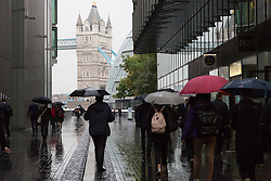 © Licensed to London News Pictures. 08/10/2014. London, UK. Commuters and City workers with umbrellas are caught in heavy rain as they arrive at work near Tower Bridge in central London this morning. Photo credit : Vickie Flores/LNP