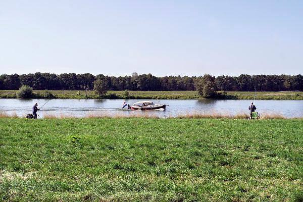 Nederland, the netherlands, Arcen, 1-9-2018Ondanks de langdurige droogte is de rivier de maas nog goed bevaarbaar. De Maas wordt via stuwen en sluizen kunstmatig op peil gehouden. Door de lage aanvoer uit Belgie wordt er minder vaak geschut zodat de scheepvaart niet veel last heeft van laagwater, behalve vetraging vanwege wachttijd bij het schutten . Vissers op de oever proberen wat vis te vangen .Foto: Flip Franssen