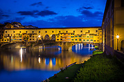 "The river Arno and Ponte Vecchio bridge in Firenze (Florence), Italy.<br /> -----<br /> Captured with a Canon 5D Mk III camera and Canon EF 24-105/4L IS lens  <br /> -----<br /> Florence (Italian: Firenze) is the capital city of the Italian region of Tuscany and of the province of Florence. The Ponte Vecchio (""Old Bridge"") is a Medieval stone closed-spandrel segmental arch bridge over the Arno River, in Florence, Italy, noted for still having shops built along it, as was once common. Butchers initially occupied the shops; the present tenants are jewellers, art dealers and souvenir sellers. The Ponte Vecchio's two neighbouring bridges are the Ponte Santa Trinita and the Ponte alle Grazie. The bridge spans the Arno at its narrowest point where it is believed that a bridge was first built in Roman times, when the via Cassia crossed the river at this point. The Roman piers were of stone, the superstructure of wood. The bridge first appears in a document of 996. After being destroyed by a flood in 1117 it was reconstructed in stone but swept away again in 1333 save two of its central piers, as noted by Giovanni Villani in his Nuova Cronica. It was rebuilt in 1345, Giorgio Vasari recorded the tradition in his day, that attributed its design to Taddeo Gaddi, besides Giotto one of the few artistic names of the trecento still recalled two hundred years later. Modern historians present Neri di Fioravanti as a possible candidate. Sheltered in a little loggia at the central opening of the bridge is a weathered dedication stone, which once read Nel trentatrè dopo il mille-trecento, il ponte cadde, per diluvio dell' acque: poi dieci anni, come al Comun piacque, rifatto fu con questo adornamento. The Torre dei Mannelli was built at the southeast corner of the bridge to defend it.<br /> The bridge consists of three segmental arches: the main arch has a span of 30 meters (98 ft) the two side arches each span 27 meters (88 ft). The rise of the arches is between 3.5 and 4.4 meters (11½ to 14½ feet), and the spa"