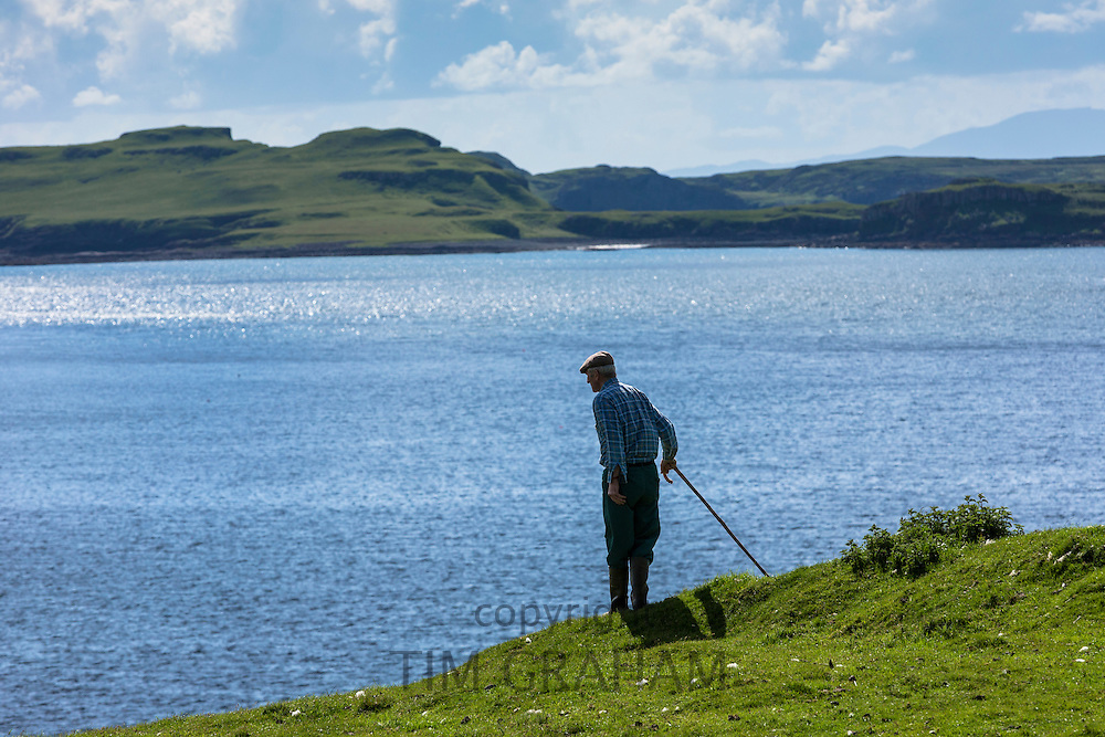 Farmer, holding shepherd crook, looks out over Loch Harport near Coillure on Isle of Skye in the Highlands and Islands of Scotland