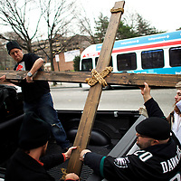 """Supporters (L-R) Jason Krieck, 38, Ryan Bolli, 42, and Nando Fuselli, 38, assist Michael Grant, 28, """"Philly Jesus,"""" in lashing the 12 foot cross to a truck following his 8 miles cross walk through North Philadelphia to Center City as part of a Christmas walk to spread the true message of the holiday in Philadelphia, PA on December 20, 2014.  As many as a half dozen others joined him for numerous miles as he trekked southward down Broad Street.  Some shouted """"Praise Jesus!"""" and """"Thank you for doing this!""""at the sight.  Nearly everyday for the last 8 months, Grant has dressed as Jesus Christ, and walked the streets of Philadelphia to share the Christian gospel by example.  He quickly acquired the nickname of """"Philly Jesus,"""" which he has gone by ever since."""