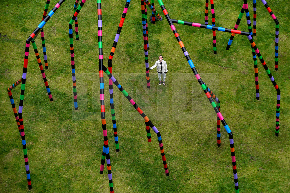 """© Licensed to London News Pictures. 16/07/2020. LONDON, UK.  A staff member poses at the unveiling of """"My World and Your World"""", by major contemporary London-based, Irish artist Eva Rothschild.  The new 16m high public sculpture in Lewis Cubitt Park in King's Cross resembles a lightning bolt, painted in black, purple, pink, orange, green and red stripes.  The coronavirus lockdown caused the April 2020 launch to be postponed, but the unveiling has been able to go ahead now that certain lockdown restrictions have been eased by the UK government.  Photo credit: Stephen Chung/LNP"""