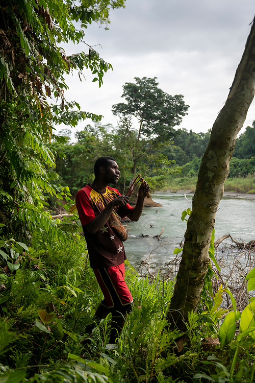 Patrick carries a slingshot as he looks for birds on the Clay River near the village of Likan in Papua New Guinea's East Sepik Province. (June 21, 2019)